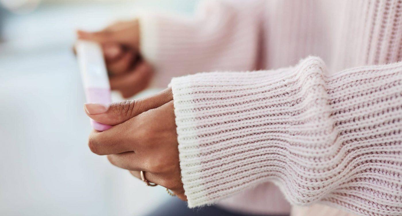 Frau mit Ovulationstest in der Hand